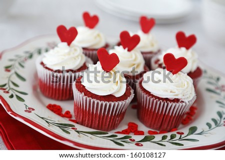 Red velvet cupcakes decorated for Christmas with red hearts - stock photo