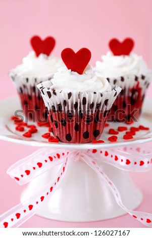 Red velvet cupcakes with cream cheese frosting decorated with red chocolate hearts - stock photo