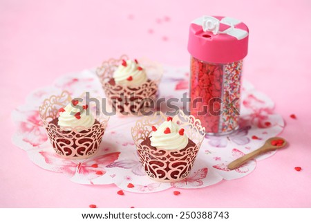 Red Velvet Cupcakes with Cream Cheese Frosting served in lace cupcake wrappers and decorated with sugar hearts, pink paper napkin and assorted colour sugar sprinkles, on a pink background. - stock photo