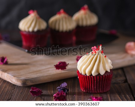 red velvet cupcakes with cream cheese icing decorate with dry flowers on wood board - stock photo