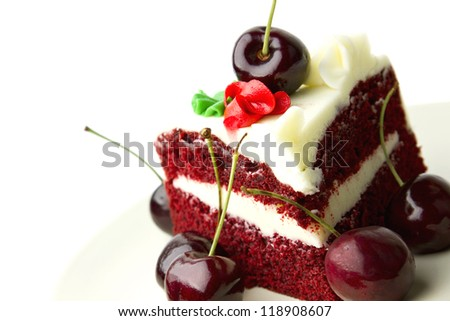 Red velvet layer cake with white frosting garnished with fresh cherries against white background. - stock photo