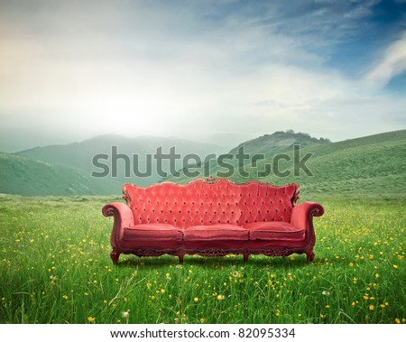 Red velvet sofa on a green meadow - stock photo