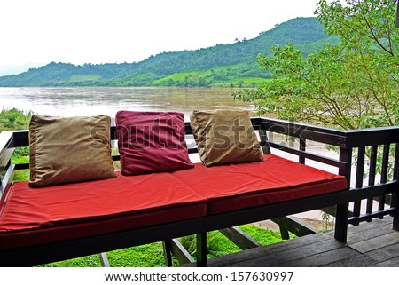 Red Velvet Sofa with Green Mountain Background, Chiang Rai , Thailand - stock photo