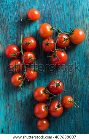 Red vibrant vine tomatoes on blue chopping board, from above - stock photo