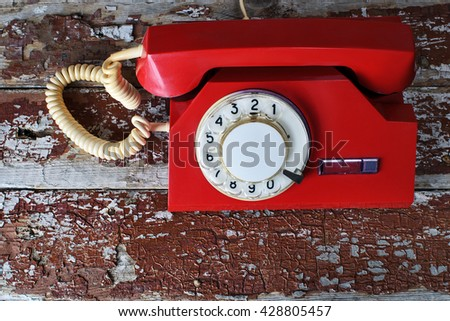 Red vintage phone on wooden background close-up, top view - stock photo