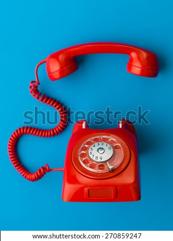 red vintage phone with handset off the hook, on blue background - stock photo
