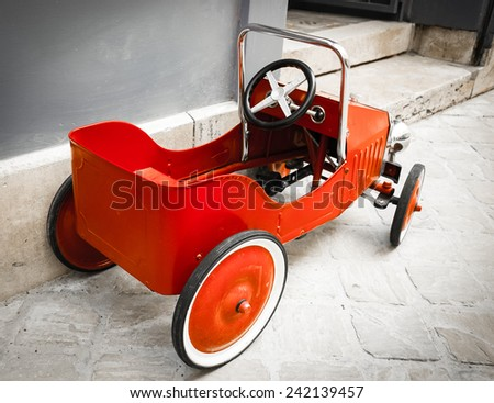 Red vintage toy car near entrance to the house. Back and side view. Aged photo.  - stock photo