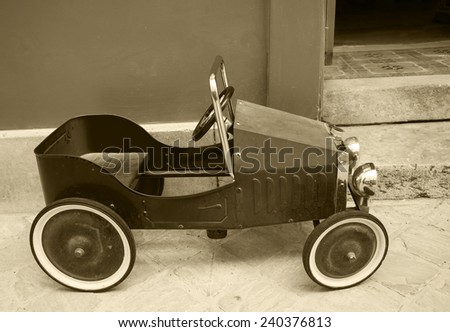 Red vintage toy car near entrance to the house. Side view. Aged photo. Sepia. - stock photo