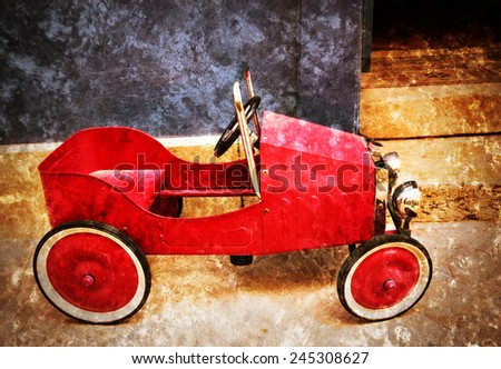 Red vintage toy car near entrance to the house. Side view. Retro aged photo with scratches. - stock photo