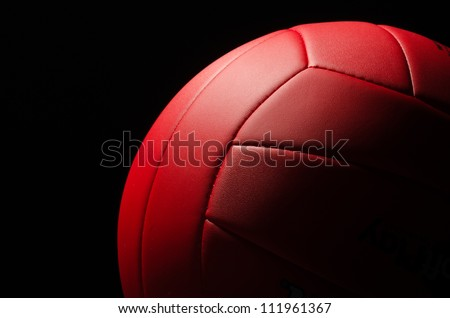 Red volley ball against a  black background - stock photo