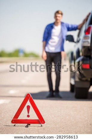 Red warning triangle with a broken down car on the road. - stock photo