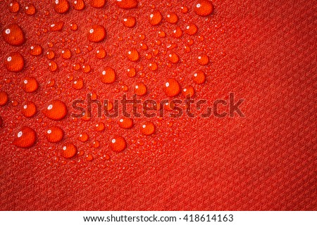 Red waterproof fabric close up with water beads - stock photo