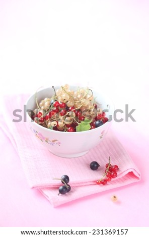 Red, White and Black Currants in a bowl, on a pink napkin and light pink background. - stock photo