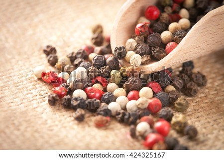 Red, white and black pepper in a wooden spoon - stock photo