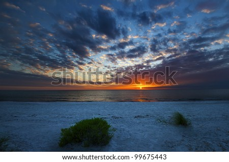 Red, White and Blue A red sunset under a blue sky on a white beach at Florida, USA. - stock photo