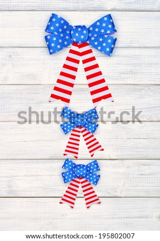 Red White and Blue American Flag Bow Decorations in center or middle on Rustic White Wood Board Background.    Horizontal  - stock photo