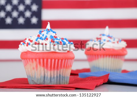 Red, white and blue cupcakes with american flag in background - stock photo