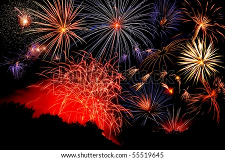 Red, white and blue fireworks against a black sky. - stock photo