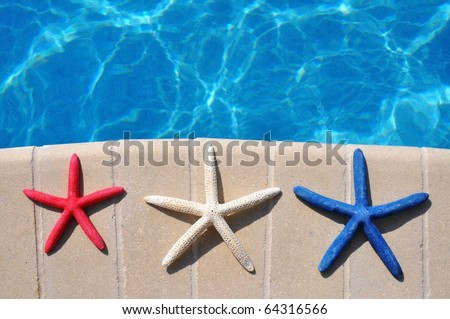 Red, White and Blue Starfish sitting by swimming pool. Room for your text - stock photo