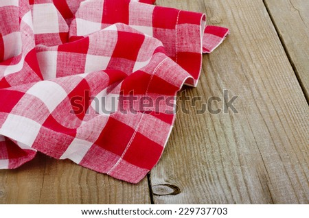 red-white checkered tablecloth in an old wooden table - stock photo