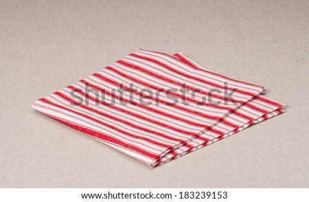 Red White Folded Napkin On Natural Linen Background - stock photo