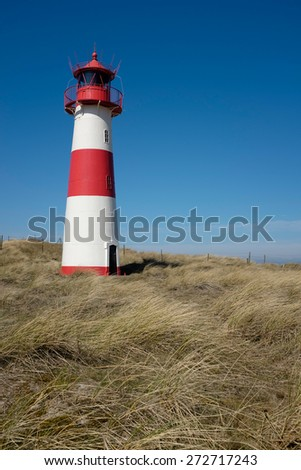 Red white Lighthouse in dune grass with blue sky - stock photo