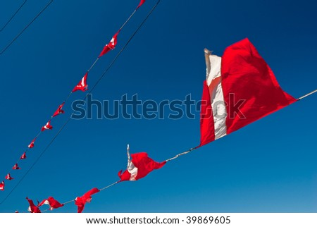 Red-white triangular ship flags flap in the breeze against a deep clear sky - stock photo