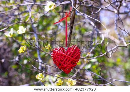 Red wicker heart hanging from tree branch with yellow spring flowers and foliage blurred in background; Valentine's Day and love concept - stock photo