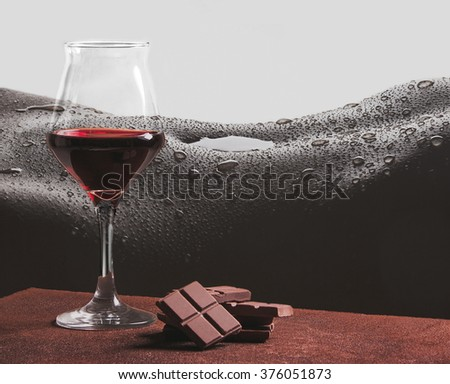 Red wine and chocolate with girl chest and water drops - stock photo