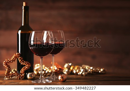 Red wine and Christmas ornaments on wooden table on wooden background - stock photo