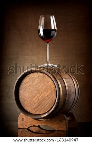 Red wine and glass with wooden barrel - stock photo