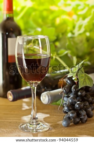 Red wine and grape on the wood surface, outdoor - stock photo