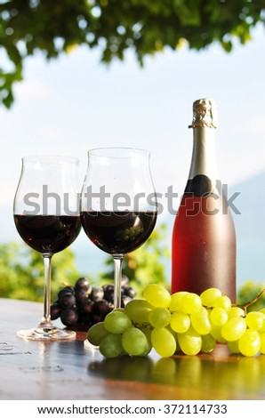Red wine and grapes against vineyards in Lavaux region, Switzerland - stock photo