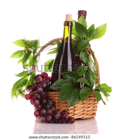 red wine and grapes in a basket isolated on white - stock photo