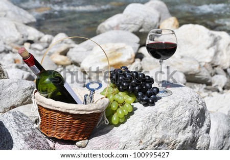 Red wine and grapes served at a picnic. Verzasca valley, Switzerland - stock photo