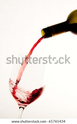 Red wine being poured into a glass white backround - stock photo