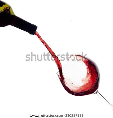 Red wine being poured into balloon glass isolated on white. Splash.  - stock photo