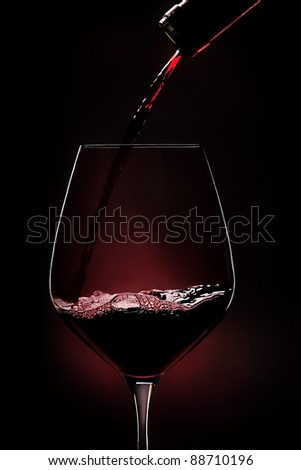 Red wine being poured into wineglass on black background. - stock photo