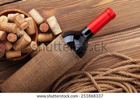 Red wine bottle and bowl with corks on wooden table background - stock photo