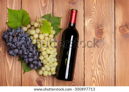 Red wine bottle and bunch of grapes on wooden table background - stock photo