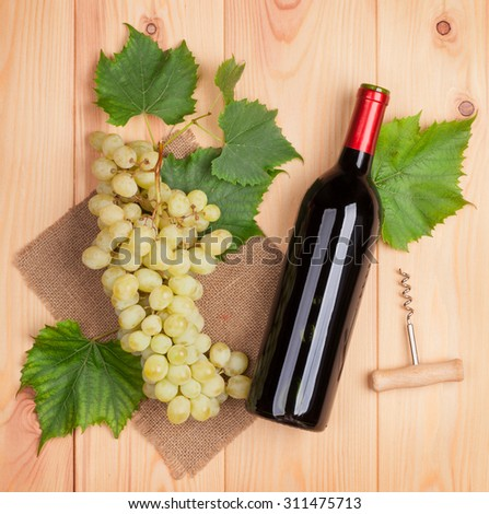 Red wine bottle and bunch of white grapes on wooden table background - stock photo