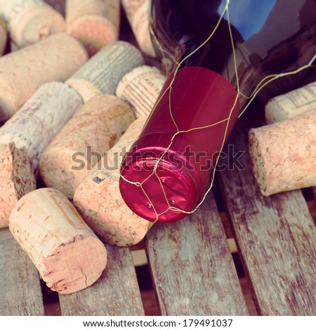 red wine bottle and corks on wooden table - stock photo