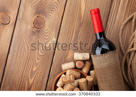 Red wine bottle and corks over wooden table background. Top view with copy space - stock photo
