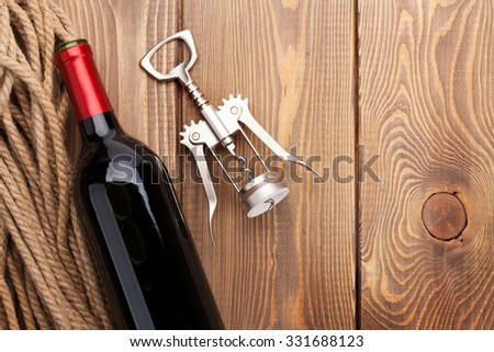 Red wine bottle and corkscrew on wooden table background. Top view with copy space - stock photo
