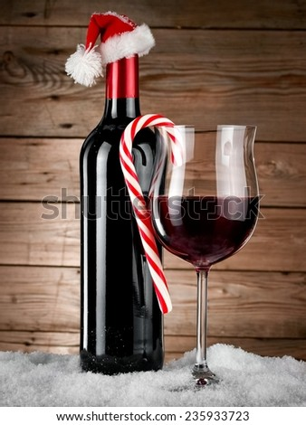Red wine bottle and glass with Xmas lollipop in snow on wooden background - stock photo