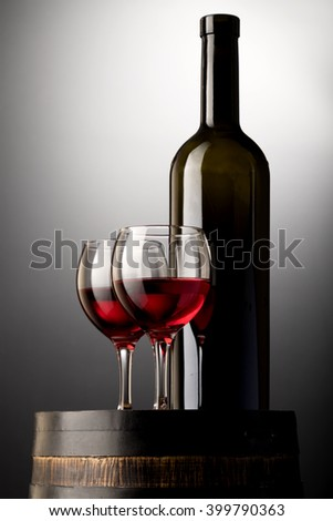 Red wine bottle and wine glasses on wodden barrel isolated on black - stock photo
