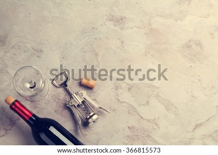 Red wine bottle, glass and corkscrew on stone table. Top view with copy space. Toned - stock photo