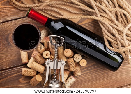 Red wine bottle, glass, corks and corkscrew. View from above over rustic wooden table background - stock photo