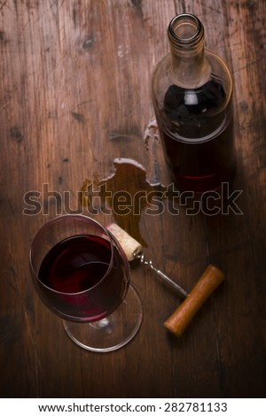 Red wine bottle, glass of wine and corkscrew - stock photo