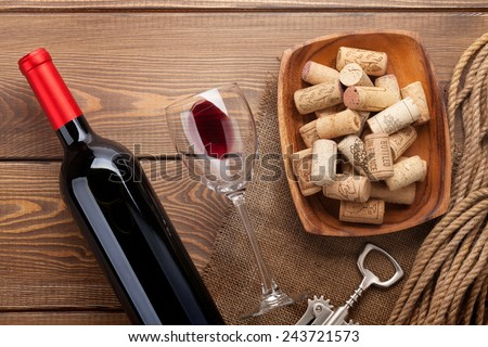 Red wine bottle, glass of wine, bowl with corks and corkscrew. View from above over rustic wooden table background - stock photo